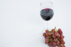 Close-up of red bunch of grapes with glass of red wine. On white background Stock Photography