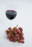 Close-up of red bunch of grapes with glass of red wine. On white background Stock Photo