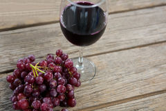 Close-up of red bunch of grapes with glass of red wine. On wooden table stock photography
