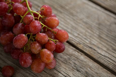 Close-up of red bunch of grapes with water droplets. On wooden table royalty free stock photo