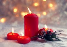 Close up of red candles and holiday wreath. Bokeh background with a shallow depth of field. Royalty Free Stock Images