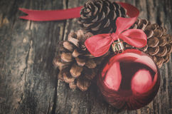 Close up of red christmas ball. And pine cone on old wooden table with vintage and vignette tone Royalty Free Stock Image