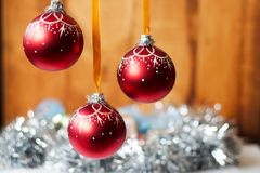 Close up of a red Christmas decoration balls on wooden and shiny background . Close up of a red Christmas decoration balls against purple background Royalty Free Stock Images
