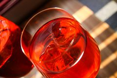 Close up of red cocktail with ice cubes in wine glass stock images