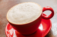 Close-up of red coffee mug with frothed milk. Close-up of a red plate and mug with coffee and frothed milk on an old wooden table Royalty Free Stock Photo