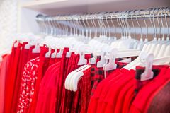 Close up red color Clothes on hangers in shop, butique. Make Outfit set. Shopping Mall. Shopper. Sales. Shopping Center. Selective. Focus. space for text Royalty Free Stock Photo
