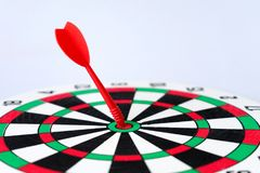 Close up red dartboard. With arrow in center focused point isolated on white background represents business goal concept Stock Photography