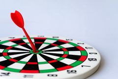 Close up red dartboard. With arrow in center focused point isolated on white background represents business goal concept Stock Photos