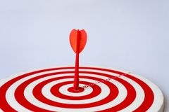 Close up red dartboard. With arrow in center focused point isolated on white background represents business goal concept Stock Image