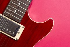 Close-up of red electric guitar on pink background. Musical concept of guitar music. royalty free stock image