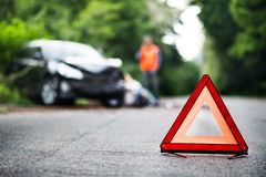 A close up of a red emergency triangle on the road in front of a car after an accident. A close up of a red emergency triangle on the road in front of a damaged stock photography
