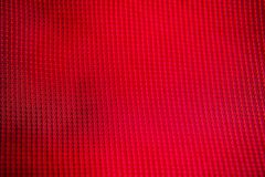 Red fabric texture. A close up of a red fabric with square stitching Royalty Free Stock Image