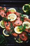 Closeup of red fish sliced with slices of lemon and dill. A delicious dish is prepared royalty free stock image