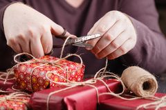 Close-up of red gift box. Christmas gifts wrapping, background of people decorating presents. Holiday, handmade, love, surprise co. Ncept Royalty Free Stock Photography