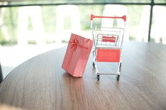 Close up red gift box and shopping cart on table for shopping and e-commerce concept stock photography