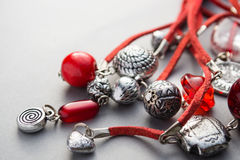 Close up of red glass beads and silver charms Royalty Free Stock Images