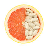 Close up of red grapefruit and pills isolated. Vitamin concept Stock Photos