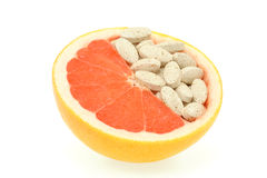 Close up of red grapefruit and pills isolated Stock Images