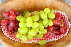 Close up of red and gree grapes on a wooden plate Stock Images