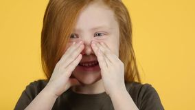 Close-up red-haired child screaming putting his hands to his face, slow motion. Close-up red-haired child screaming putting his hands to his face looking into stock video