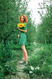 Close up. The red-haired girl in the green dress smiles and looks at the camera. In her hands she holds a bouquet.