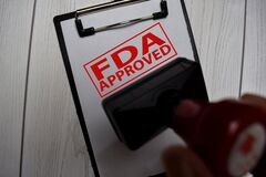 Close up Red Handle Rubber Stamper and text FDA Approved isolated on White Background. Selective focus on FDA Approved