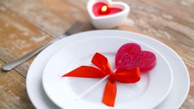 Close up of red heart shaped lollipop on plate. Valentines day and romantic dinner concept - close up of red heart shaped lollipop on set of dishes and candle stock footage