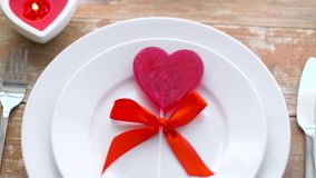 Close up of red heart shaped lollipop on plate. Valentines day and romantic dinner concept - close up of red heart shaped lollipop on set of dishes and candle stock video