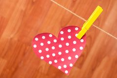 Close up red hearth with polka dots and yellow clothespin hung on hemp rope on a wooden background Royalty Free Stock Image