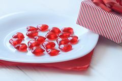 Close up.red hearts on white plate and gift box on light background. Holiday concept Royalty Free Stock Image