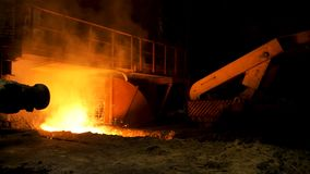 Close up for red, hot molten iron at the steel enterprise, heavy industry concept. Stock footage. Melted steel flowing royalty free stock photography