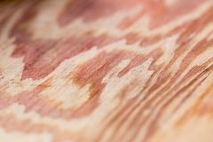 Close up of red hued grain on wood plank Stock Image