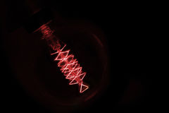 Close up on red  light bulb glowing in dark Royalty Free Stock Photography