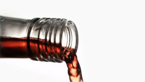 Close up, red liquid in a super slow motion flowing of the glass bottleneck. Against a white background stock video