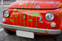 Close-up on a red mini vintage car; Red Bug. A red mini vintage car with butterflies and flowers painted on it. The car is situated in the center of Hermannstadt Royalty Free Stock Images