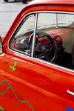 Close-up on a red mini vintage car's wheel. With butterflies and flowers painted on the car. The car is situated in the center of Hermannstadt (Sibiu) in Royalty Free Stock Photography