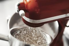 Red mixer and boiling sugar syrup in metal pot. stock photography
