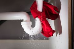 Red Napkin Tied Under The Leakage Sink Pipe. Close-up Of Red Napkin Tied Under The Leakage White Sink Pipe stock photo