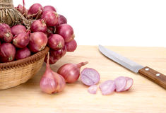 Close up red onion or shallots in wooden basket with sliced onion on wooden chopping block Stock Images