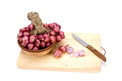 Close up red onion or shallots in wooden basket with sliced onion on wooden chopping block Royalty Free Stock Photos
