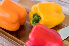 Close up of bell peppers on cutting board. Close up of red, orange and yellow bell peppers on a wooden cutting board with a kitchen knife Royalty Free Stock Photos