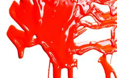 Close up of red paint. Flows of red glossy paint close-up on white background royalty free stock photography