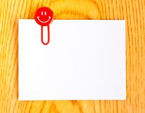 Close up of a red paper clip and white paper royalty free stock image