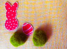 Close-up of red paper rabbit and paper egg silhouette frames against canvas background.  Stock Photo