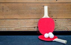 2 ping pong paddles and 3 ping pong balls against a wooden wall Royalty Free Stock Photography