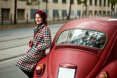 Close-up of red retro car behind and girl near it. Close-up of a red retro car behind and a cute girl near it. The girl is dressed in a coat and beret with in Royalty Free Stock Photos