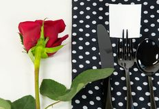 Red rose and black silverware on napkin Stock Photography