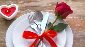 Close up of red rose flower on set of dishes. Valentines day and romantic dinner concept - close up of red rose flower on set of dishes and heart shaped candle stock footage