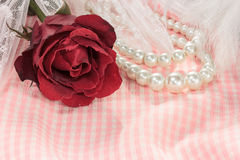 Close up red rose with pearl necklace on pink fabric background. Royalty Free Stock Photography