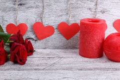 Close-up of red roses on a gray background with a garland of paper hearts and candles, the concept of a holiday. stock photo
